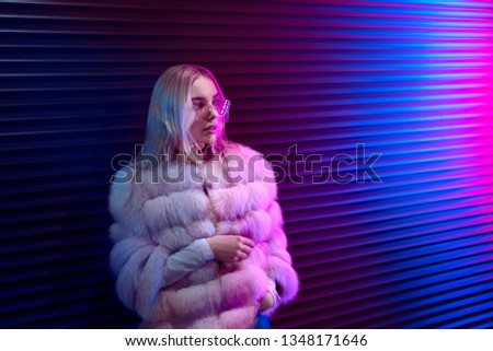 Teen hipster girl in stylish glasses and fur standing on purple street neon light wall background, female teenager fashion model pretty young woman looking at night club city light glow, back to 80s #1348171646