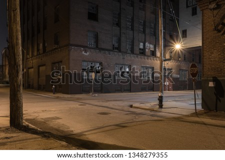 Beautiful street scene with vintage red brick factory buildings at night in a depressed urban blue collar industrial area with broken windows in St. Louis Missouri #1348279355