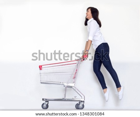 happy asian girl jump up shopping cart on white background. Potrait asian woman smile shoaholic with blank trolley for product display or sale festival concept. #1348301084