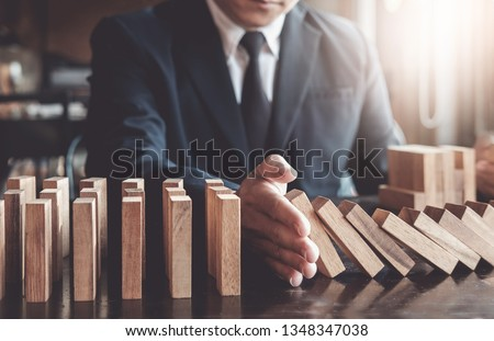 Business risk control concept, Businessman protect wooden block fall to planning and strategy in risk to business Alternative and prevent. Investment Insurance Business. #1348347038