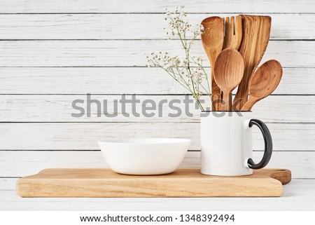 Cooking utensils and cutting board on white table. Kitchen utensils background #1348392494