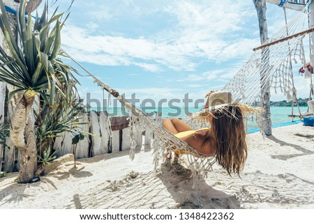 Girl relaxing in hammock in tropical beach cafe, hot sunny day at paradise island #1348422362