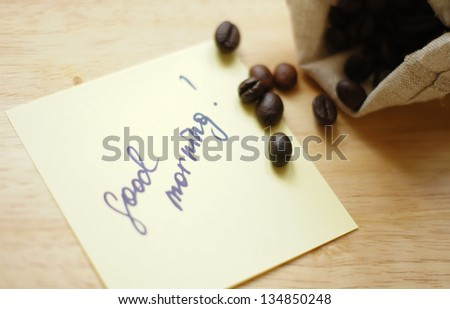 Coffee beans and Good morning note on the wooden desk