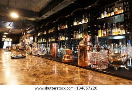 Classic bar counter with bottles in blurred background Royalty-Free Stock Photo #134857220