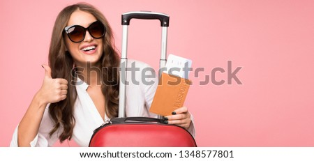 Time to travel. Woman with tickets showing thumb up over pink background #1348577801