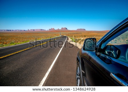 Monument Valley Arizona, USA - June 2017: Beautiful sunny day view of the Monument Valley in Arizona, USA, with vintage car on the road. #1348624928