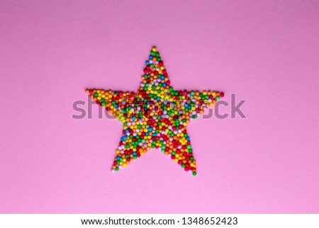 Star shape made from candy hundreds and thousands sprinkles bright multi coloured on a pink background #1348652423