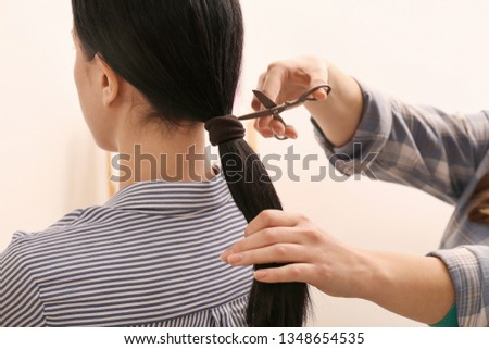Woman cutting hair of young girl. Concept of donation #1348654535