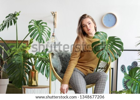 Portrait of beautiful woman with green tropical leaves indoors #1348677206