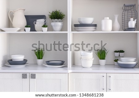 Open cupboard with clean dishes in kitchen #1348681238