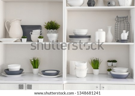 Open cupboard with clean dishes in kitchen #1348681241