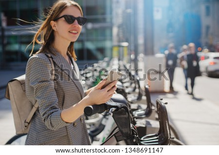 Happy stylish woman taking bike via bike renting services in the city center, Happy smiling student using bike sharing app on smart phone outdoor #1348691147