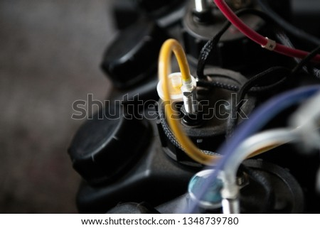 Close-up of colorful inkjet cartridges connected with cables to printing machine in printing house #1348739780