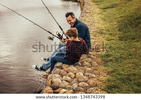 Happy father and son fishing in a lake holding fishing rods. Man sitting with his son on the banks of a lake enjoying fishing holding fishing rods. #1348743398