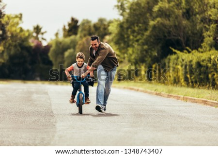 Kid riding a bicycle while his father runs along holding the bicycle. Happy kid having fun learning to riding a bicycle with his father. #1348743407