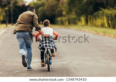 Rear view of a boy riding a bicycle while his father runs along holding the kid. Father teaching his son to ride a bicycle. #1348743410