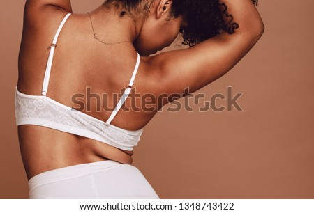 Rear view of sensual african woman posing in lingerie. Female wearing underwear on brown background. #1348743422