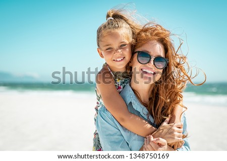 Smiling mother and beautiful daughter having fun on the beach. Portrait of happy woman giving a piggyback ride to cute little girl with copy space. Portrait of kid embracing her mom during summer. #1348750169