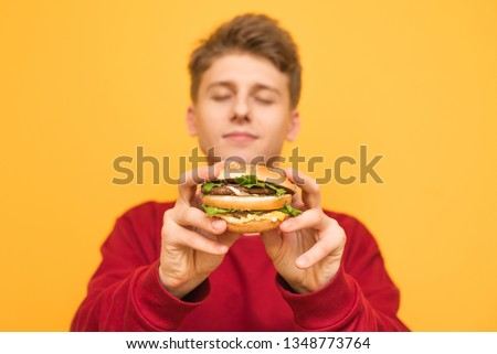Handsome guy with his eyes closed shows a delicious large burger to the camera, holds in his hands, isolated on a yellow background.Focus on an appetizing burger in the hands of a young man. Fast food #1348773764