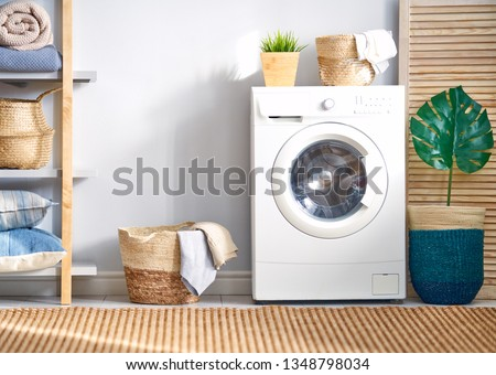 Interior of a real laundry room with a washing machine at home #1348798034