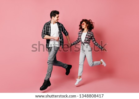 Full length shot of jumping couple having fun together. Studio photo of young people running on pink background.