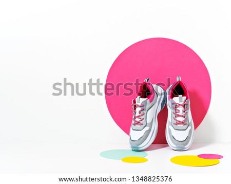 Bright lit scene with chunky sneakers and huge confetti. Colorful casual wear or footwear. Minimalist fashion fitness creative concept. Royalty-Free Stock Photo #1348825376