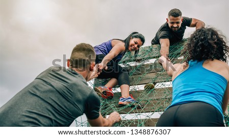 Group of participants in an obstacle course climbing a net Royalty-Free Stock Photo #1348876307