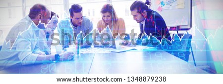 Stocks and shares against serious photo editors discussing about photos on table