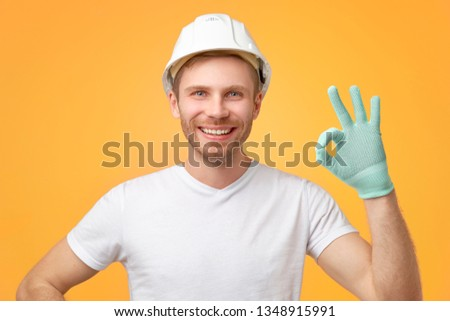 Pleased confident European man with broad smile, uniform, shows okay gesture, dressed in t-shirt and construction helmet. Isolated over white background.  #1348915991