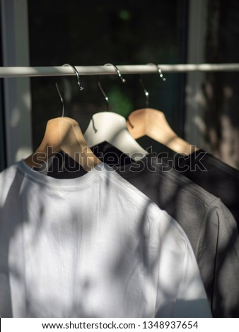 White, grey and black t-shirts on hangers, close up view #1348937654