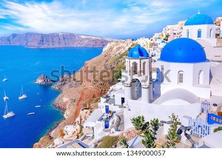 Beautiful Oia town on Santorini island, Greece. Traditional white architecture  and greek orthodox churches with blue domes over the Caldera in Aegean sea, Greece. Scenic travel background. #1349000057