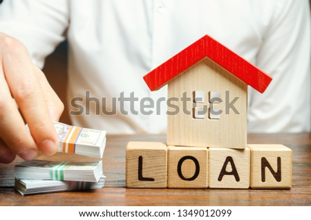 Wooden blocks with the word Loan, house and money in the hands of a businessman. The concept of buying an apartment or house in debt. Mortgage credit lending. Payment of interest rates. Saving money #1349012099