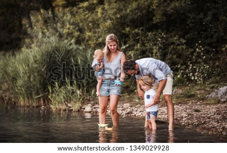 Young family with two toddler children outdoors by the river in summer, playing. #1349029928