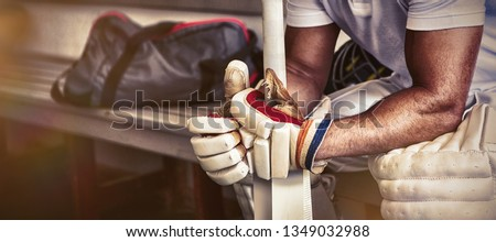 Stressed cricket player sitting on bench at locker room, Close-up