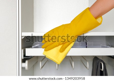 Hand in rubber protective glove with microfiber rag is cleaning cupboard in room. Household chores. Сleaning or regular clean up. #1349203958