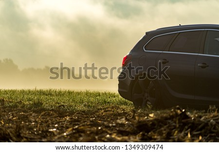 Hilpoltstein, Germany - 10.02.2017: Car in a field on a foggy sunrise #1349309474