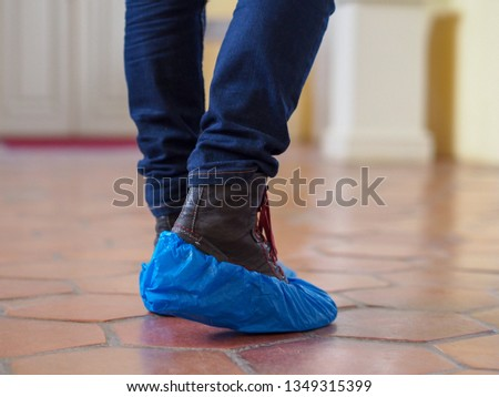 Man with blue shoe covers worn over boots with red shoe laces standing on a tiles, closeup side view. #1349315399