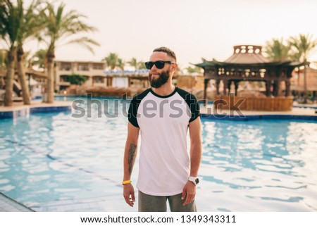 A young stylish hipster man with a beard in a white T-shirt and glasses #1349343311