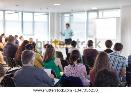 Business and entrepreneurship symposium. Speaker giving a talk at business meeting. Audience in conference hall. Rear view of unrecognized participant in audience. #1349356250