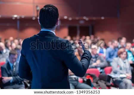 Speaker giving a talk on corporate business conference. Unrecognizable people in audience at conference hall. Business and Entrepreneurship event. #1349356253