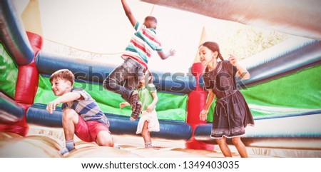 Friends jumping on bouncy castle at playground #1349403035