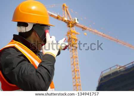 Foreman construction wearing safety vest  talking in mobile phone, yellow crane in the background #134941757
