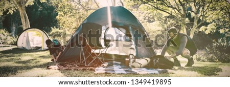 Father and son setting up the tent at campsite on a sunny day #1349419895