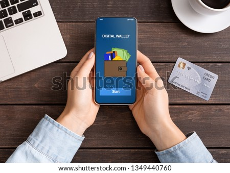 Mobile banking. Woman holding smartphone with digital wallet application. credit card on table, top view Royalty-Free Stock Photo #1349440760