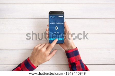 Man using Bitcoin earning application on smartphone screen, white wooden background, top view #1349440949