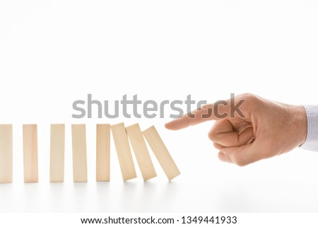 Hand pushing dominoes, white background with empty space #1349441933
