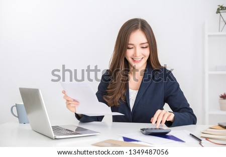 Portrait of asian business woman paying bills online with laptop in office. Beautiful girl with computer and chequebook, happy paying bills. Startup business financial calculate account concept #1349487056
