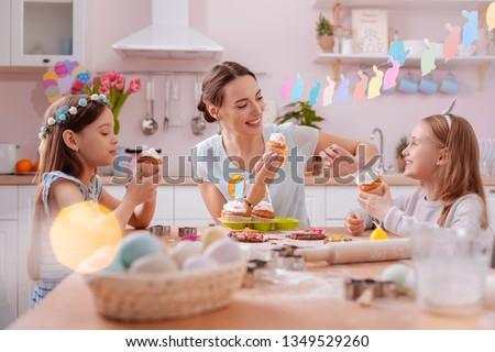 Family relaxation. Cute blonde girl keeping smile on her face while going to eat cake