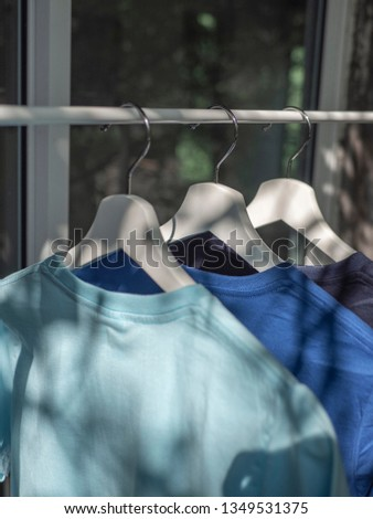 blues t-shirts on hangers, close up view #1349531375