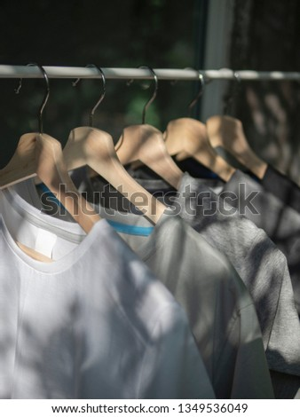 White, grey and black t-shirts on hangers, close up view #1349536049